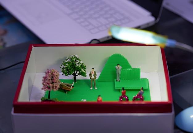Расслабьтесь модель коробки офисного пространства на размытом столе с технологическим компьютерным фоном ноутбука