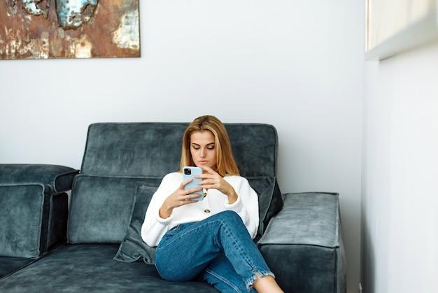 Расслабьтесь на диване дома. стиль жизни. привлекательная женщина с помощью смартфона, сидя на софе.