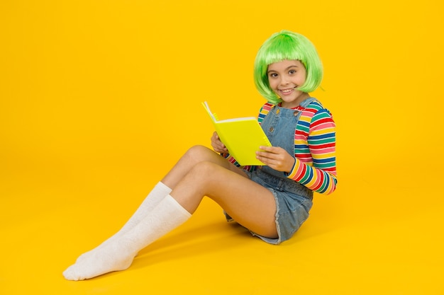 Relax and read book. adorable small child read book yellow background. cute little girl enjoy reading. you cant buy happiness but you can buy book. book store. library. bibliopole.