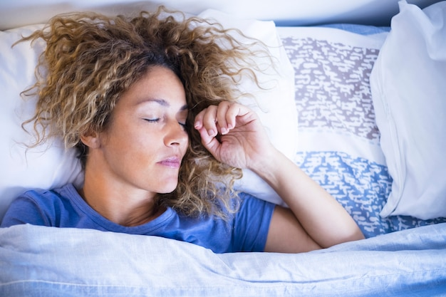 Relax and sleep concept with beautiful caucasian woman sleeping in the morning light at home or hotel