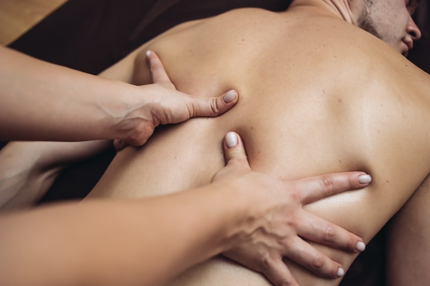 Relax tantric massage for man in four hands using aromatherapy oils