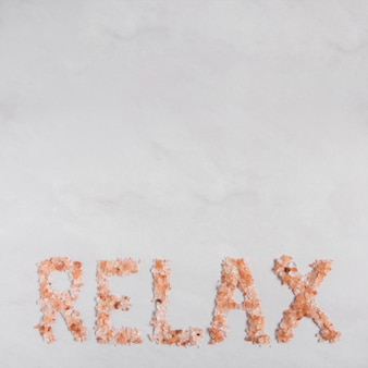Relax text made with himalayan herbal salt on white backdrop