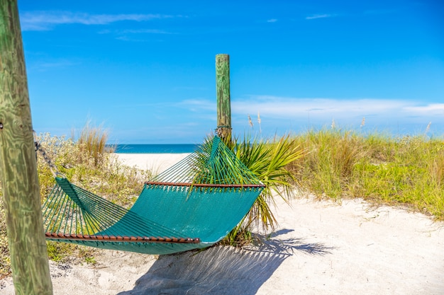 Relax with empty hammock and ocean background on tropical beach.