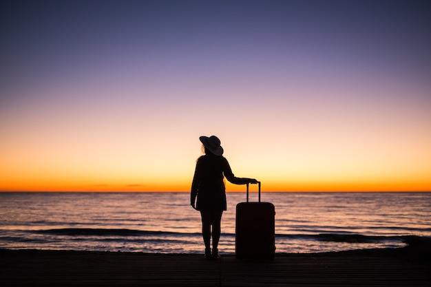 日没のシルエットでビーチでスーツケースを持つ女性をリラックスします。休日の旅行の概念。海の風景にスーツケースを持つ若い女性。