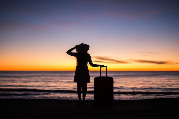 日没シルエット休日旅行コンセプト若い女性のビーチでスーツケースと女性をリラックス
