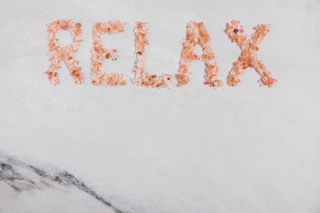 Relax word made with himalayan salt on textured background