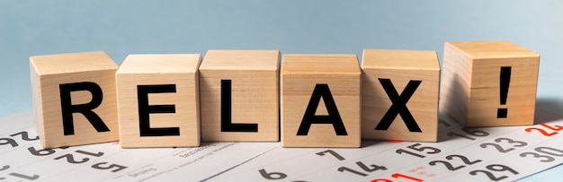黒と赤の休日の数字、バナーとカレンダーの木製の立方体のブロックに書かれたリラックスワード