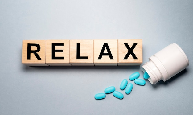 Relax word written on wooden cube blocks on gray table with jar with scattered pills