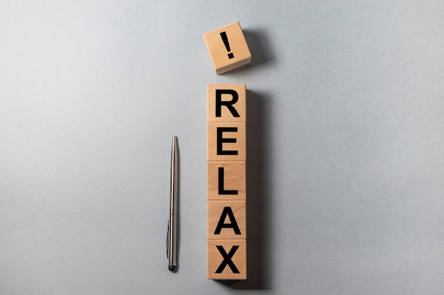 Relax word written on wooden cube blocks on office table with silver pen