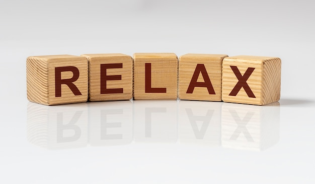 Relax word written on wooden cube blocks on white glossy table with reflection