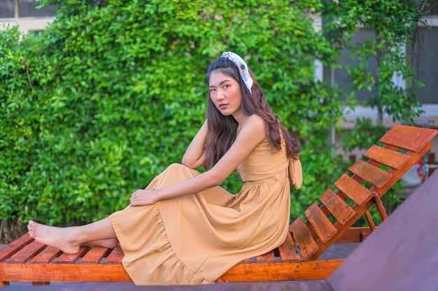 Азиатская женщина в коричневом платье relax чувствовать себя счастливым. с туризмом у бассейна