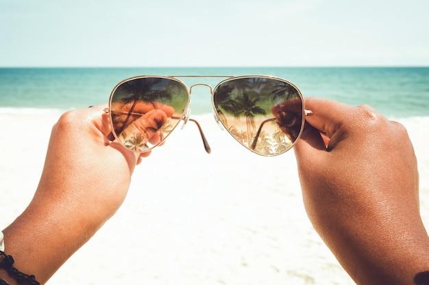 夏のリラクゼーションとレジャー-夏の熱帯のビーチでサングラスを持っている若い日焼けした女性の手。ヴィンテージカラートーン