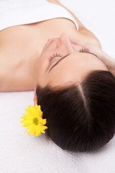 Расслабление для тела и разума. вид сверху привлекательной молодой женщины, лежащей и с закрытыми глазами, пока массажист массирует ее лицо