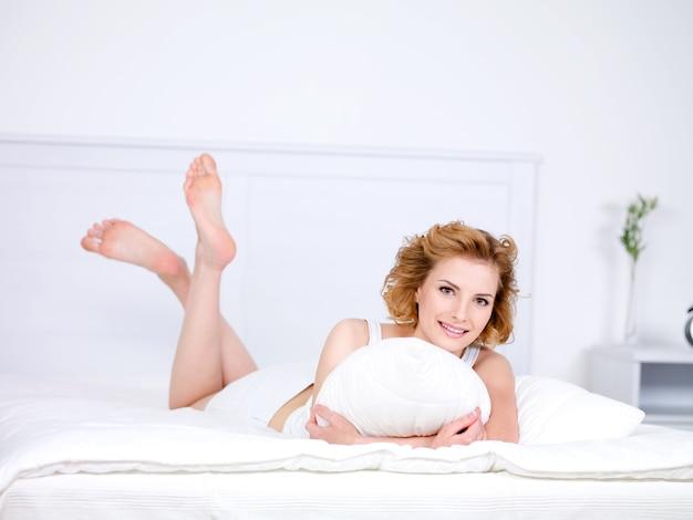 枕とベッドに横たわっている若い美しい笑顔の女性のためのリラクゼーション