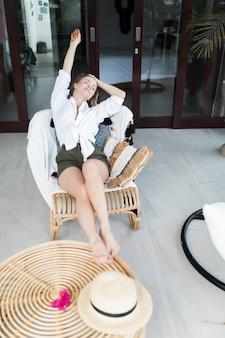 Релаксация, здоровый образ жизни, летний отпуск, отпуск женщины-фрилансера, расслабьтесь, отдыхая в удобном кресле на балконе курортного отеля, сохраняя душевное спокойствие и баланс качества собственного здоровья