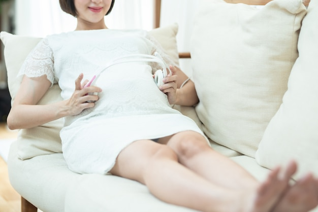 Relaxation in pregnancy. calm pregnant young asian girl listen to music mozart effect good for fetus by using headphones attached to the stomach hold earphones near belly lying on sofa at home.