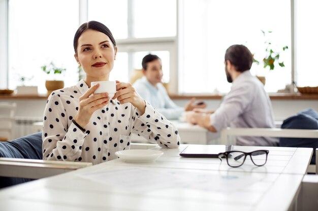 Расслабление. довольно задумчивая темноволосая молодая женщина улыбается и пьет кофе, сидя за столом и думая
