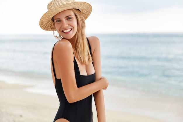リラクゼーション、夏、レジャーのコンセプト。夏の帽子と水着で幸せな若い魅力的な女性は海のパノラマビューに立ち向かい、新鮮な海の空気を吸い込み、前向きな表情と笑顔を持っています