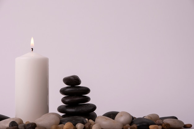 Relaxation therapy with a candle between stones