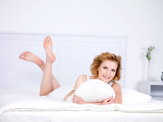 Relaxation for young beautiful smiling woman lying in a bed with pillow