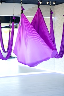 Relaxation. young woman practice in aero stretching swing. aerial flying yoga exercises practice in purple hammock in fitness club.
