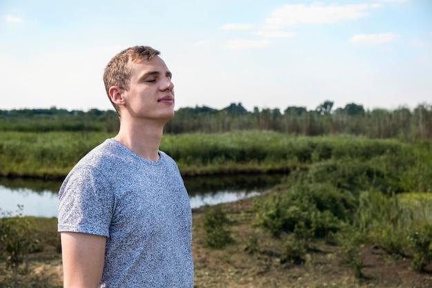 新鮮な空気を吸って、バックグラウンドで湖のあるフィールドに立って楽しんでリラックスした大人の男