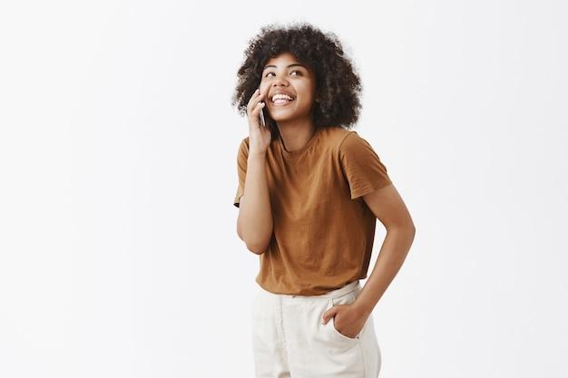 Расслабленная афроамериканская девушка весело разговаривает через смартфон, глядя вверх с беззаботной радостной улыбкой, держа руку в кармане стоя