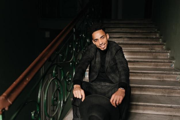 Ragazzo africano rilassato che gioca con il suo cappello. uomo nero entusiasta che si siede sulle scale in posa sicura.