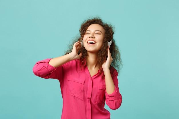 青いターコイズブルーの壁の背景に分離されたヘッドフォンで音楽を聴きながら、目を閉じてカジュアルな服装でリラックスしたアフリカの女の子。人々の誠実な感情、ライフスタイルのコンセプト。コピースペースをモックアップします。