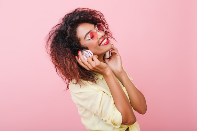 Relaxed african woman with light-brown skin listening music with eyes closed and happy face expression. trendy curly black girl in yellow cotton shirt holding earphones and smiling