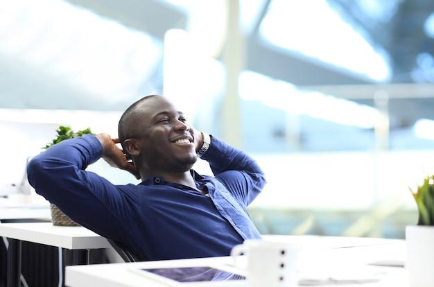 空を見ながら机に座ってリラックスしたアフリカ系アメリカ人のビジネスマン。