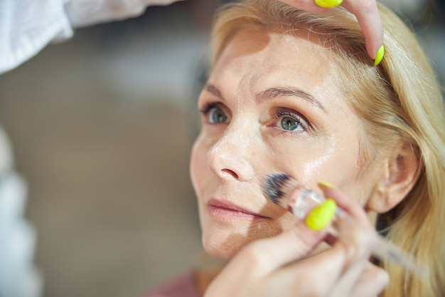 Расслабленная пожилая женщина смотрит вперед, глубоко задумавшись во время макияжа