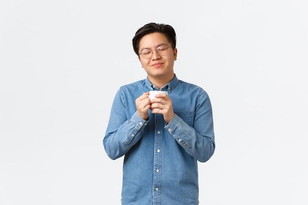 Расслабленный и счастливый улыбающийся азиатский мужчина с закрытыми глазами, наслаждаясь восхитительным ароматом кофе, держа кружку и попивая капучино, утреннюю рутину и концепцию образа жизни.