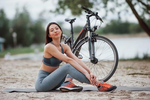 Расслаблен и доволен. велосипедистка с хорошей формой тела сидит возле своего велосипеда на пляже в дневное время