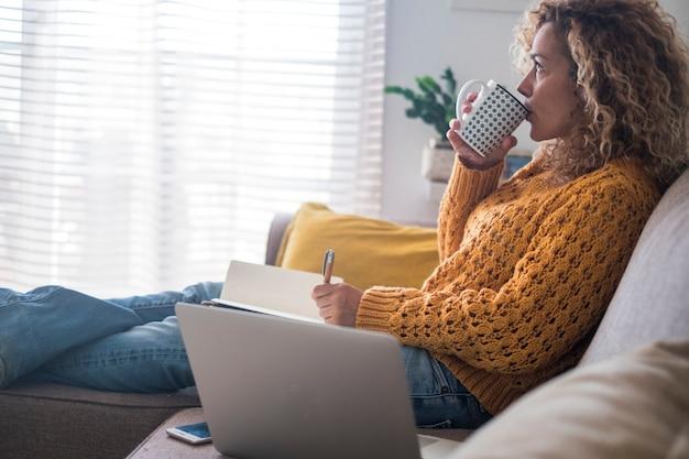 편안 하 고 걱정 성인 여성 집에서 종이와 펜 및 컴퓨터 노트북 소파에 앉아 생각 하 고. 마시는 음료