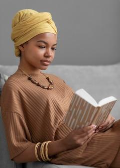 Расслабленная арабская женщина, читающая книгу дома