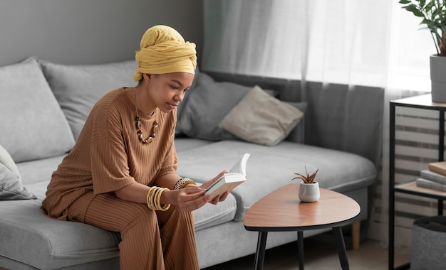 Donna araba rilassata che legge un libro a casa