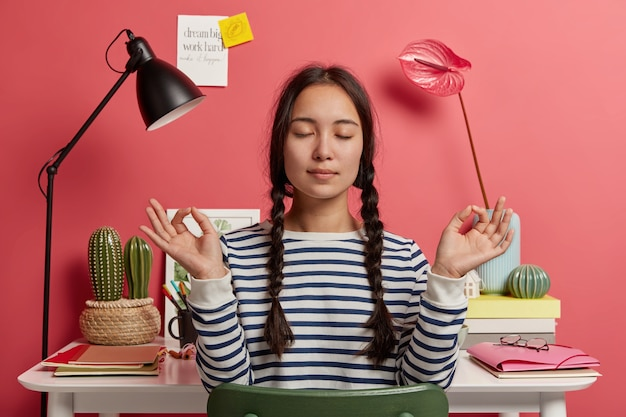 Relaxed asian woman meditates at workplace, sits in zen pose against desktop with flowers, desk lamp, notepads, wears striped casual jumper, tries to relax after work, isolated over pink background