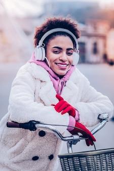 リラックスした雰囲気。彼女の自転車に座っている間彼女の顔に笑顔を保つ驚くべき若い女性