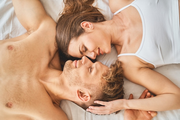 Relaxed atmosphere. pleased male person lying on the bed and touching hand of his wife