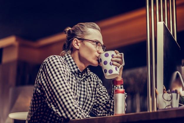 リラックスした雰囲気。半位置に座って、お茶を飲む深刻な男性