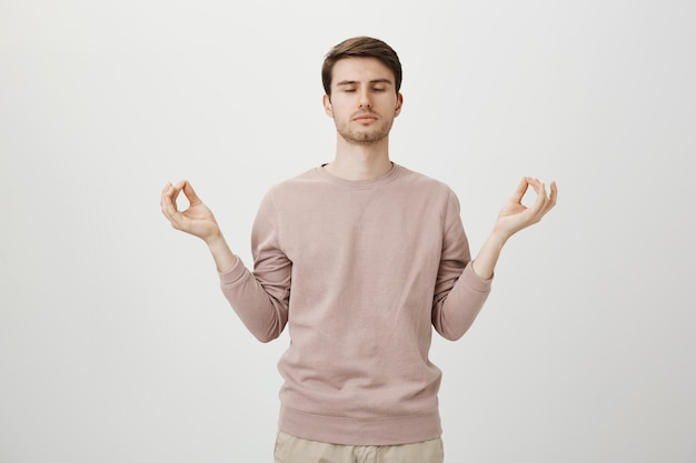 Relaxed attractive guy meditating, hold hands sideways with zen gesture
