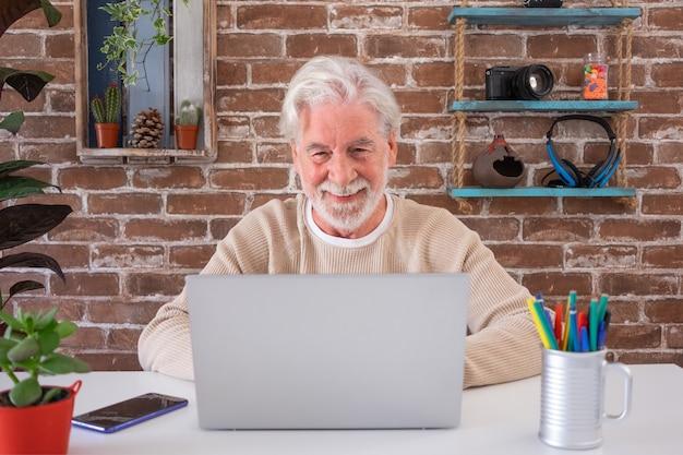 Расслабленный привлекательный старший мужчина дома с помощью портативного компьютера. кирпичная стена на фоне