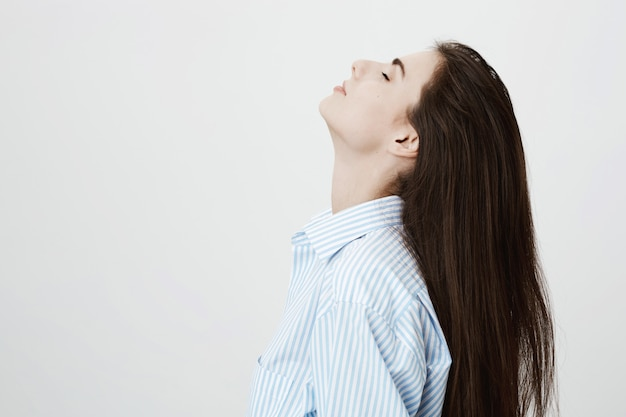 Расслабленная привлекательная женщина откидывает волосы назад и мечтательно закрывает глаза, отдыхая