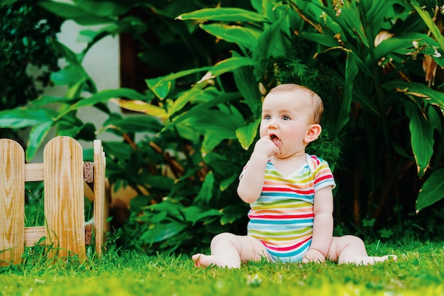 Relaxed baby enjoying the sensation of noticing the freshness of the grass on his bare feet.