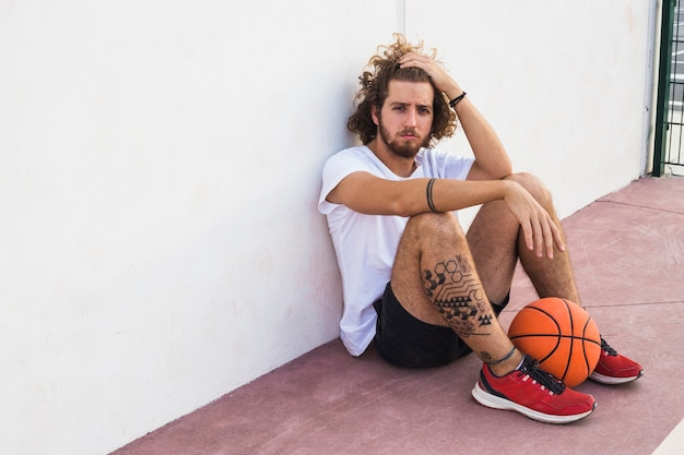 Relaxed basketball player sitting with ball