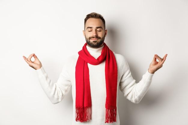 Расслабленный бородатый парень стоит в мире, медитирует с закрытыми глазами, стоит на белом фоне в красном шарфе и свитере