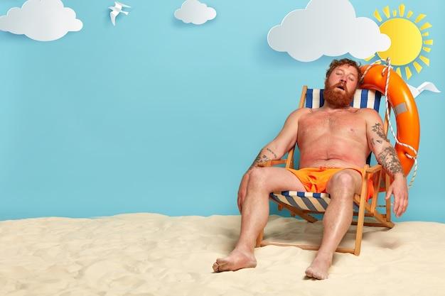 Relaxed bearded man sleeps on his deck chair, poses on beach