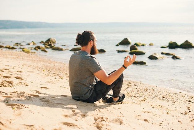 リラックスしたひげを生やしたスポーティな男がビーチで蓮華座に座っています。