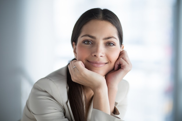 Relaxed beautiful business lady leaning on hands